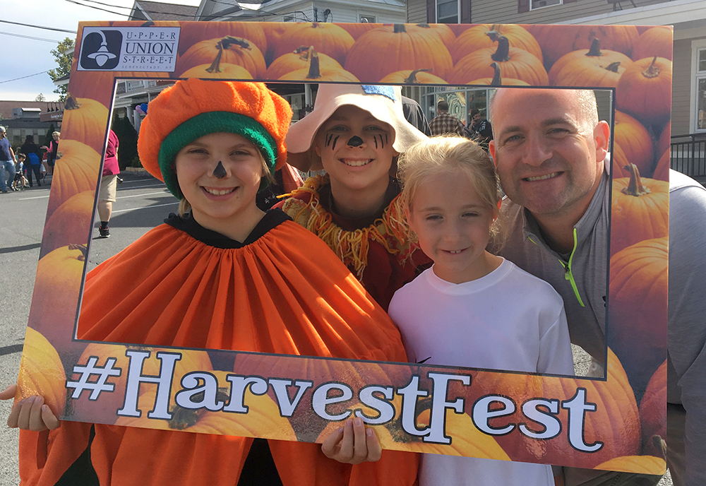 family and characters inside harvest fest frame